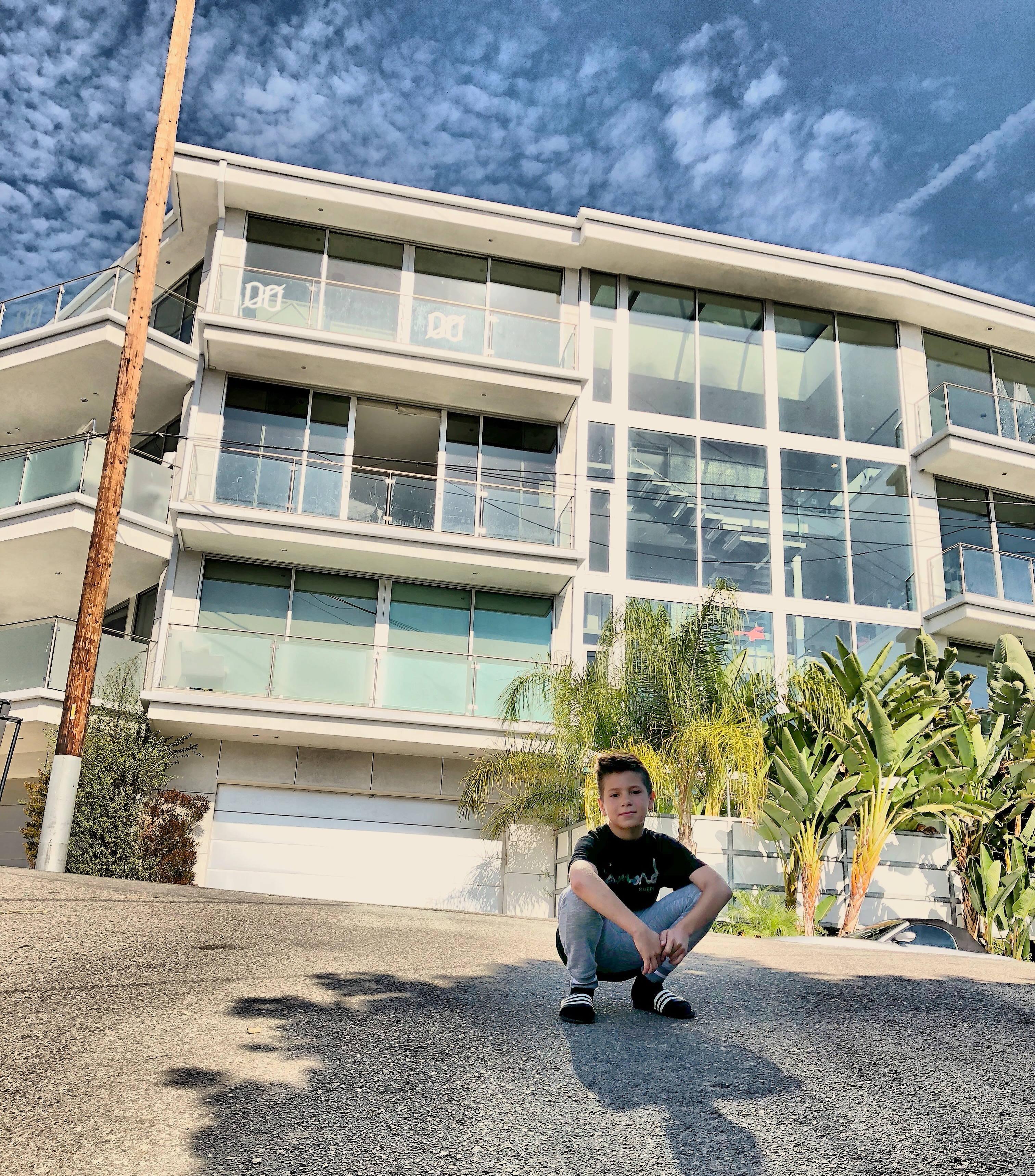 A boy in front of a Hollywood mansion